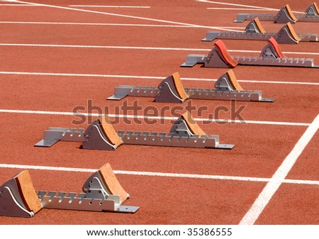 Runners   - get ready!  Running starting blocks at track and field event - stock photo