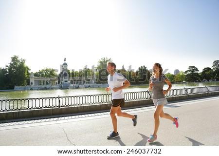 Runners jogging running in Madrid El Retiro city park. Exercising woman and man runner training on jog living healthy lifestyle in Buen Retiro Park, Parque el Retiro in Madrid, Spain, Europe. - stock photo