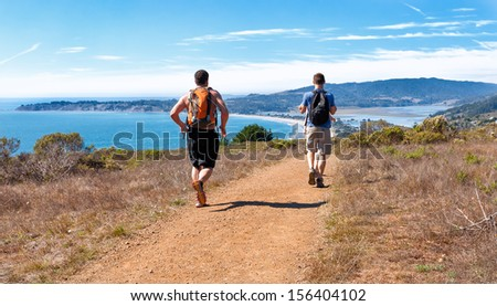 Runners on a scenic trail with a view of the Pacific Ocean and Stinson Beach north of San Francisco - stock photo