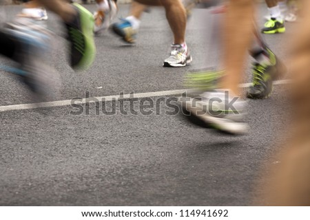 Runners running in city marathon, motion blur on sporty legs - stock photo
