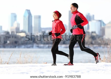 Runners running in winter snow with city skyline background. Healthy multiracial young couple. Asian woman runner and Caucasian man running with Montreal skyline, Quebec, Canada - stock photo