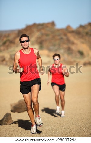 Runners running training for marathon competition in beautiful desert landscape. Two men sport fitness models during exercise run. - stock photo