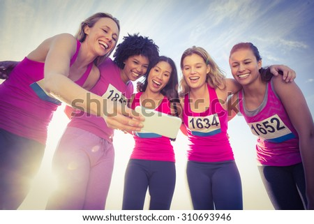Runners supporting breast cancer marathon and taking selfies in parkland - stock photo