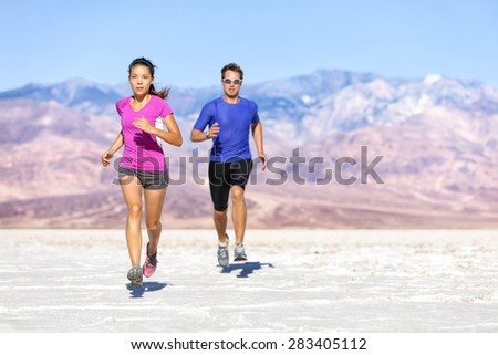 Runners trail running on dry desert landscape. Couple of fit athletes sprinting in compression activewear wearing sports clothing sweating in hot weather. Full length people in dramatic nature. - stock photo