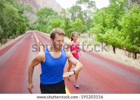 Runners training - young multiracial couple running exercising concentrated on road in beautiful nature. Caucasian fitness model man checking time or pulse on heart rate monitor watch. - stock photo