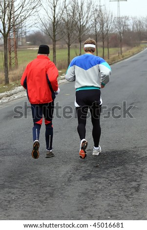 Runners while training for a competition in winter - stock photo