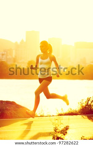 runners - woman running outdoors in sunshine. Young woman jogging in city of Montreal, Quebec, Canada, - stock photo