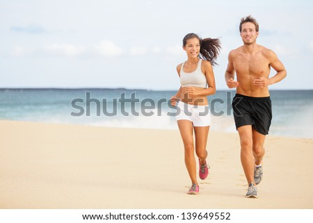 Runners. Young couple running on beach. Athletic attractive people jogging in summer sport shorts enjoying the sun exercising their healthy lifestyle. Multiethnic couple, Asian woman, Caucasian man. - stock photo