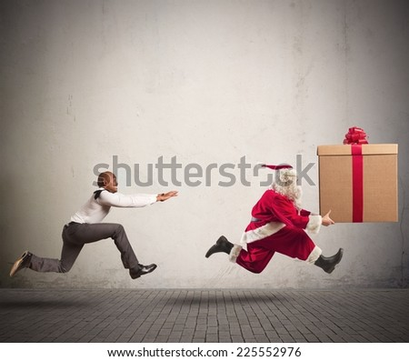 Running angry man chasing Santa Claus with a big present - stock photo