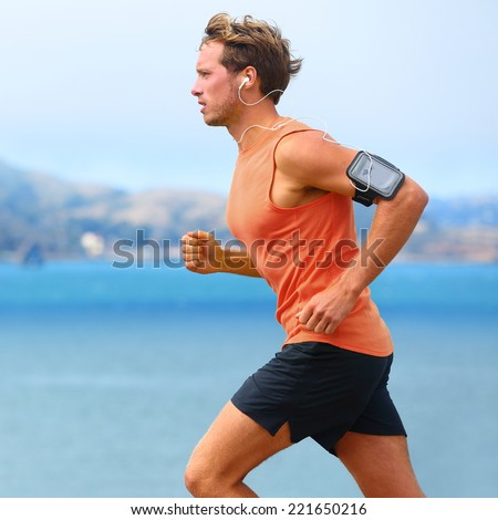 Running app on smartphone. Male runner listening to music jogging with armband for smart phone. Fit man fitness model working outdoor by water. - stock photo