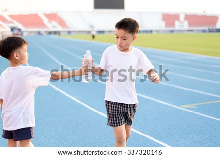 Running Asian boy taking bottle of water from another boy on the race track. - stock photo