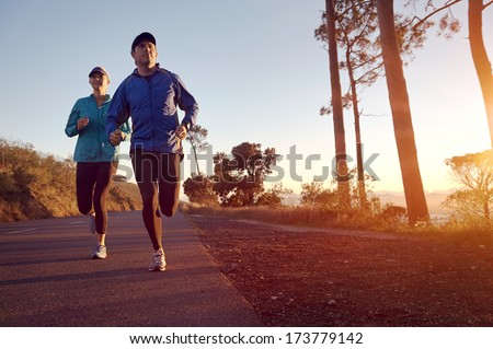 Running at sunrise couple exercising for marathon and workout fitness - stock photo