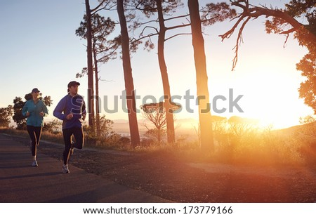 Running at sunrise couple exercising for marathon and workout fitness - stock photo