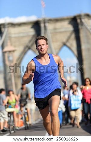 Running athlete training cardio on Brooklyn bridge, New York City, NYC. Male caucasian runner running. Young adult doing his fitness workout routine in afternoon sunset among many people tourists. - stock photo