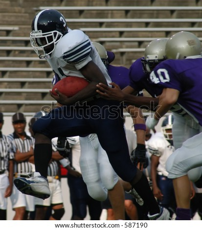 Running back breaking through tacklers at the line of scrimmage - stock photo