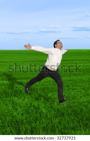 Running businessman in the meadow over clouds background - stock photo