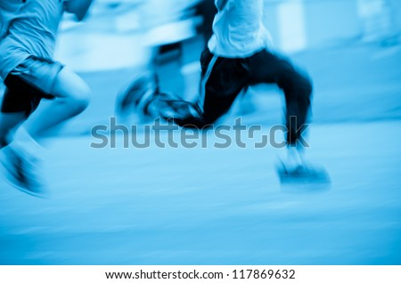 running child on sport track,blue blurred motion abstract background - stock photo