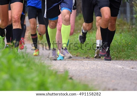 Running competition. Group of men running on a walkway. Close up of legs.