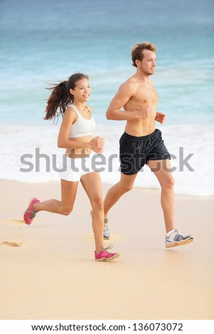 Running couple jogging on beach. Runners sport training together outside on beautiful beach. Fit athlete fitness model man and attractive woman. Multiracial, Asian female and Caucasian male runner. - stock photo