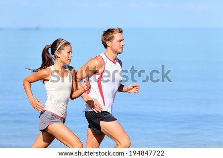 Running couple jogging on beach. Runners training together. Man and woman joggers exercising outdoors. - stock photo
