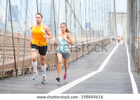 Running couple. Runners jogging outside on run. Asian woman and Caucasian man runner and fitness sport models training outdoors on Brooklyn Bridge, New York City, USA. - stock photo