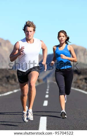 Running couple. Runners outdoor jogging workout on road beautiful landscape. Fit athletes training, Caucasian man, Asian woman. - stock photo