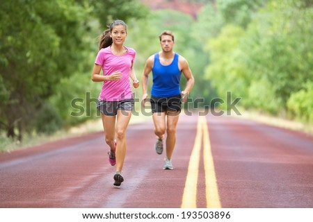Running couple training outdoors on road in wood for marathon. Mixed race pretty young female and fit caucasian handsome man in their twenties. Lifestyle full figure - stock photo