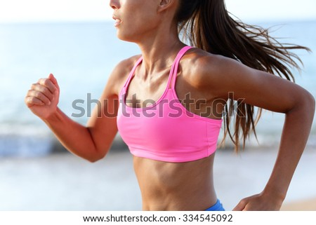 Running Determined Sprinting Woman Runner On Beach. Midsection of sporty woman training on beach. Young female is wearing pink sports bra. Determined runner is exercising on sunny day. - stock photo
