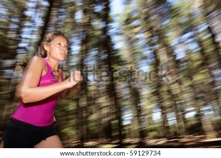 Running, Female runner running fast at great speed in forest. Motion blurred image of beautiful Asian / Caucasian woman athlete sprinting outdoors in tank top. - stock photo
