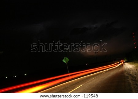 Running from the tornado-car streaks down the highway as lightning and tornado descend in distance