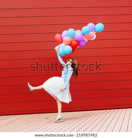 Running girl with colorful balloons in her hand. Outside. Red background - stock photo