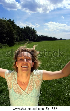 Running girl Young woman does the splits on a grassy paddock. Extended arms - stock photo
