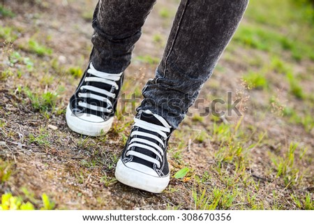 Running gumshoes are on the legs, person walking on earth, low angle - stock photo