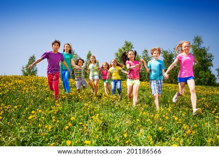 Running happy kids holding hands in green field