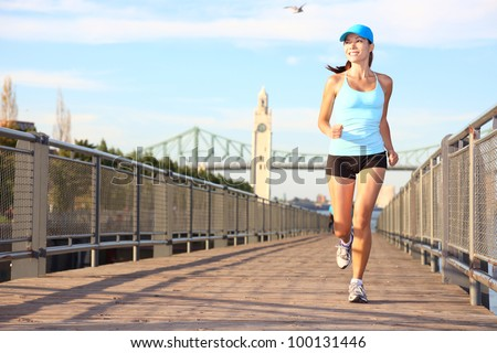 Running in city. Woman runner sport fitness model working out jogging smiling happy in Old Port of Montreal, Quebec, Canada. Beautiful young multiracial female runner. - stock photo