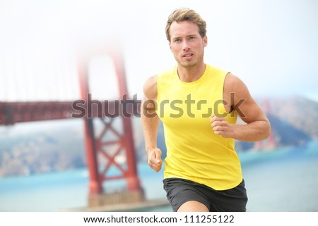 Running in San Francisco. Athlete runner working out jogging by Golden Gate Bridge, San Francisco, USA. Young fit caucasian sport fitness model. - stock photo