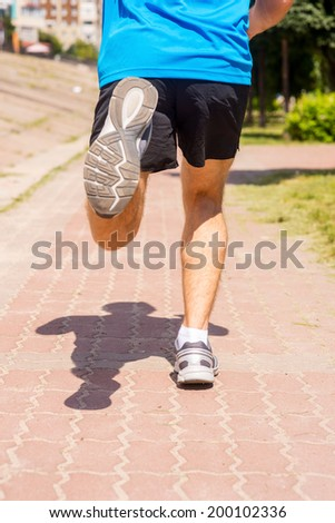 Running in sports shoes.  Rear view of men in sports shoes running