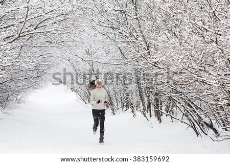 Running in the woods in winter. Beautiful young woman running jogging in the winter forest. Trees in the snow. Weather snow cloud. Fitness on the street in the winter. - stock photo