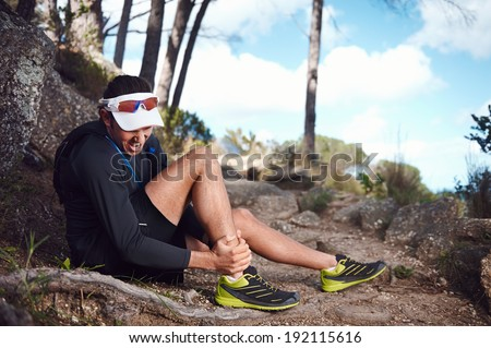 running injury for trail runner on mountain twisted ankle - stock photo