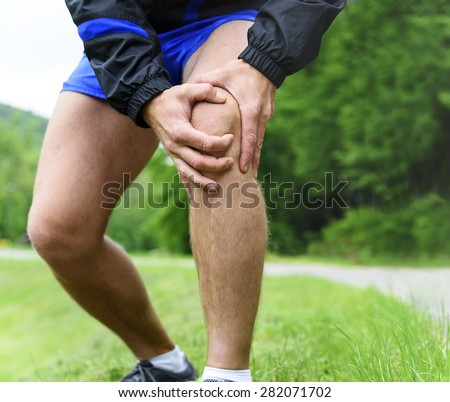 Running injury - Man out jogging with knee pain - stock photo
