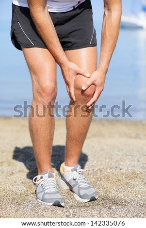 Running injury - Man out jogging with knee pain. Closed up veiw of the hands of a man out jogging on the beach clutching his knee as though in pain - stock photo