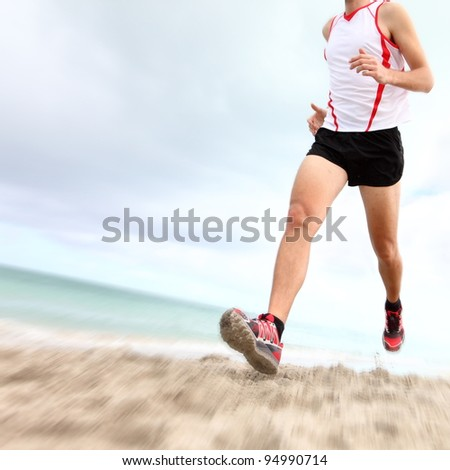 Running legs and shoes of runner jogging on beach. Caucasian sport man training for marathon. - stock photo