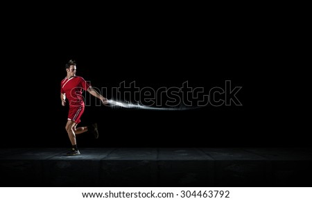 Running man in red sport wear on black background
