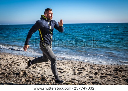 Running man jogging on beach. - stock photo