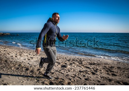 Running man jogging on beach. - stock photo
