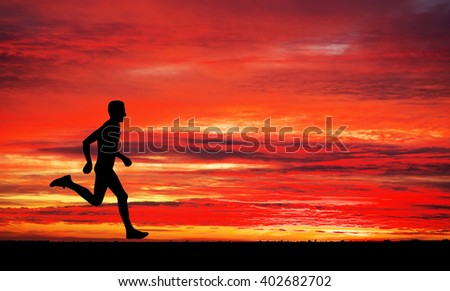 Running man on apocalyptic sunset sky background