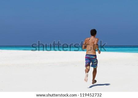 Running man on the beach - stock photo