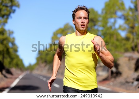 Running man sprinting for success on run. Male athlete runner training at fast speed. Muscular fit sport model sprinter exercising sprint on forest road. Caucasian fitness model in his 20s. - stock photo
