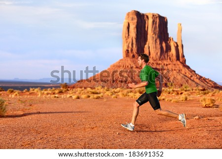 Running man sprinting in Monument Valley. Athlete runner cross country trail running outdoors in amazing nature landscape. Fit male sports model in fast sprint at speed outdoors, Arizona Utah, USA. - stock photo
