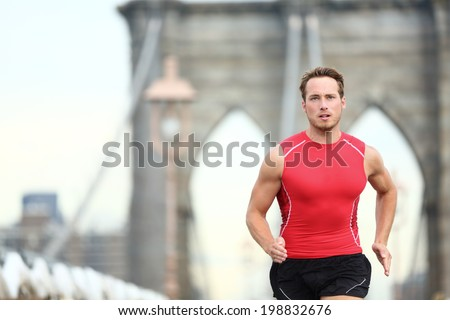 Running man sprinting in New York City. Runner on training run outside. Caucasian male runner and fitness sport model in sprint wearing compression clothing on Brooklyn Bridge, New York City, USA. - stock photo
